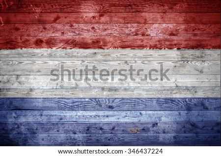 A vignetted background image of the flag of Netherlands painted onto wooden boards of a wall or floor. - stock photo