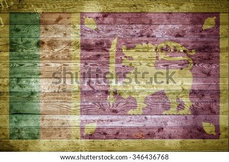 A vignetted background image of the flag of Sri Lanka onto wooden boards of a wall or floor. - stock photo