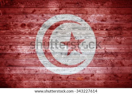 A vignetted background image of the flag of Tunisia onto wooden boards of a wall or floor. - stock photo