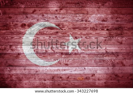 A vignetted background image of the flag of Turkey onto wooden boards of a wall or floor. - stock photo