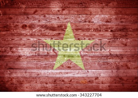 A vignetted background image of the flag of Vietnam onto wooden boards of a wall or floor. - stock photo