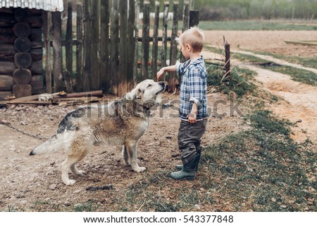 A village boy playing with a dog