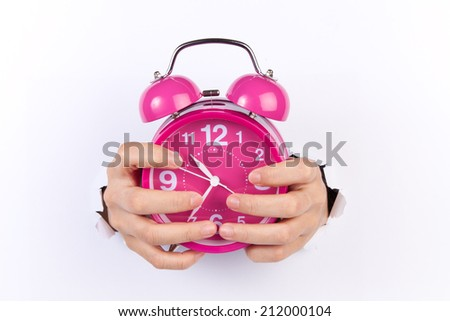 a vintage alarm clock on white background and a human hand which is about to show - stock photo