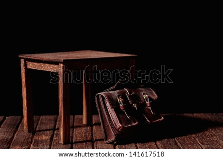 a vintage bag under an old and wooden table - stock photo