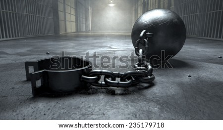 A vintage ball and chain with an open shackle on an old prison cell block floor lit by overhead lights - stock photo