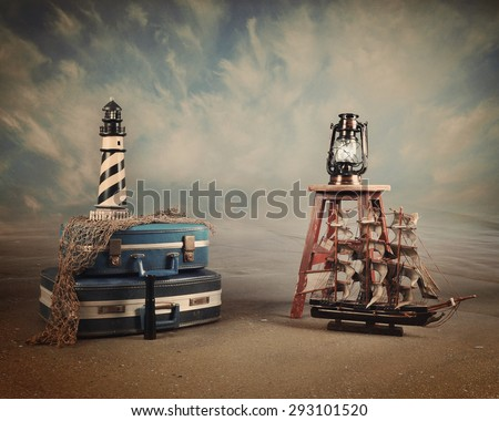 A vintage beach sea background with a little ship, lighthouse and suitcases for a travel or destination idea. Add your text to the copyspace. - stock photo