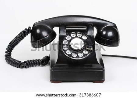 A vintage black rotary phone.