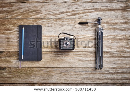 a vintage camera, tripod and journal - stock photo