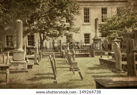 A vintage-cast, high-contrast, grunge-textured, desaturated capture of an ancient, colonial era, church yard, cemetery in Charleston, South Carolina. - stock photo