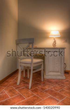 a vintage desk with a chair and a lamp - stock photo