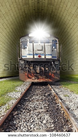 A vintage diesel powered train with a lighted head lamp emerging from a railway tunnel.