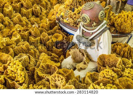 A vintage diving suit with helmet with natural sponges in the background, Greece - stock photo