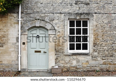 A vintage door and window on the facade of an old English cottage stone wall. - stock photo
