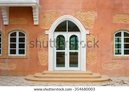 A vintage door and window on the facade of stone wall