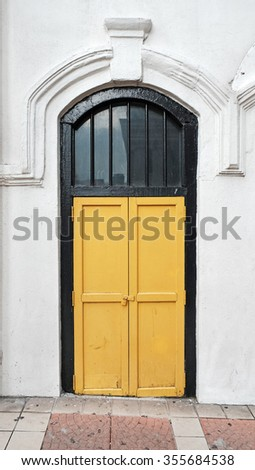 A vintage Dutch neoclassical design yellow timber door and mason archway.  - stock photo