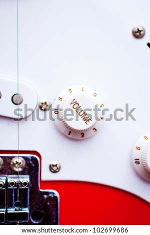A vintage electric guitar's volume control dial. Focus on 'volume'.