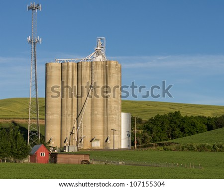 A vintage grain elevator shares space with a modern cell phone tower - stock photo