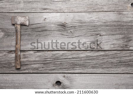 A vintage hatchet displayed on a background of grey barn board.  - stock photo