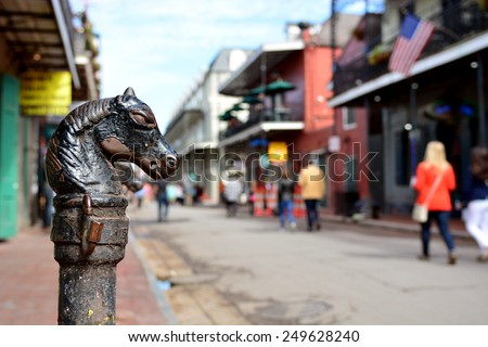 A vintage horse head hitching post on Bourbon Street in the historic New Orleans French Quarter with shallow depth of field.