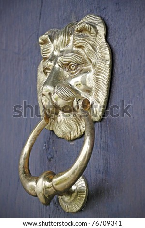 A vintage lion design brass door knocker on a wooden door. - stock photo