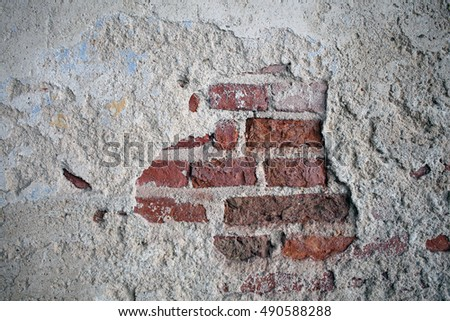 A vintage look of cracked concrete with red brick wall background