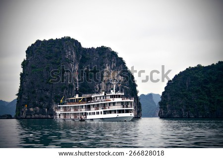 A vintage looking steam boat floats in the waters of the UNESCO World Heritage Site, Halong Bay in Vietnam. The photo has a retro filter to enhance the vintage feel of the image. - stock photo