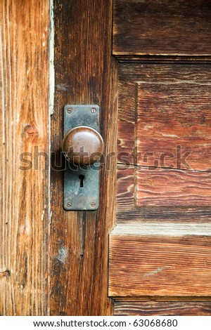 A vintage mortise lockset on an old wooden door. - stock photo