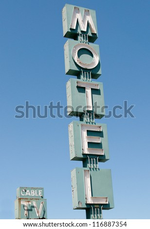 A vintage motel sign stands along the road