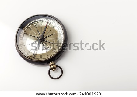 A vintage(old) compass on the glossy table(desk) isolated white at the studio. - stock photo