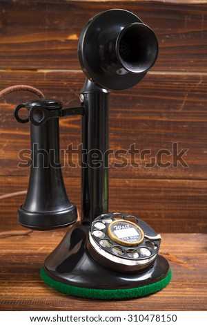 A vintage, old-fashioned, antique candlestick telephone on a wood background - stock photo