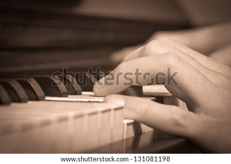 a vintage photo of a man playing on a piano - stock photo