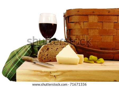 a vintage picnic basket on a rustic pine table with bread, cheese, and wine with a pure white background