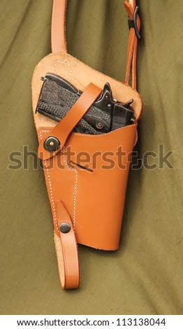 A Vintage Pistol Hand Gun Hanging in a Leather Holster. - stock photo