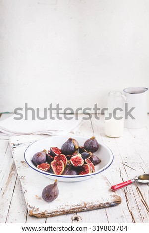 A vintage plate with juice and fresh ripe blue figs and plate for cream cheese and jars of honey. Ingredients for Preparing delicious dessert with fresh ripe figs. Rustic style. See series recipe.  - stock photo