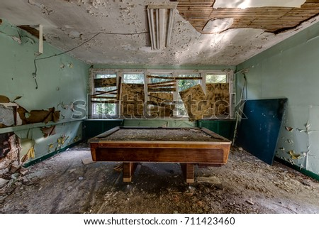 A vintage pool table resides in a deteriorated game room inside an abandoned hospital.