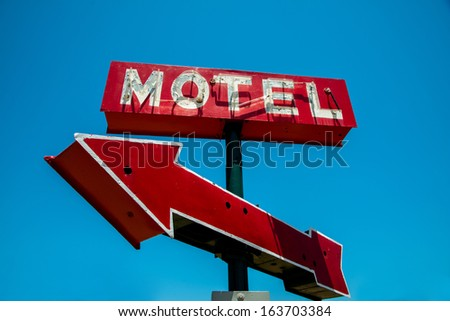 A vintage red neon hotel sign with a red arrow and a sky blue background - stock photo