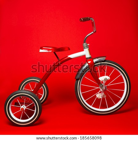 A vintage red tricycle on a bright red background - stock photo