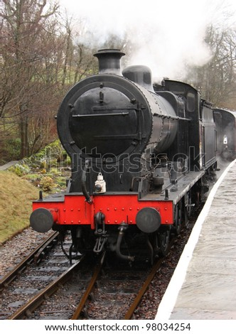 A Vintage Steam Engine Pulling Away from it's Carriages. - stock photo
