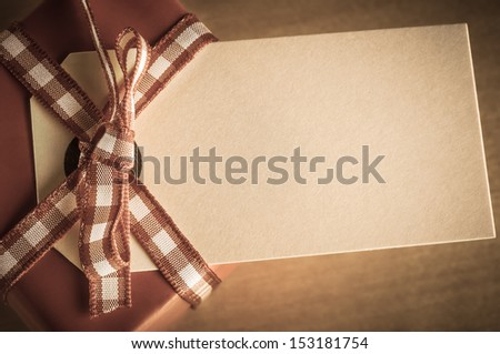 A vintage style desaturated red Christmas gift box, with gingham ribbon bow and an old parcel tag label.  Shot overhead with label facing upwards and left blank to provide copy space.  - stock photo