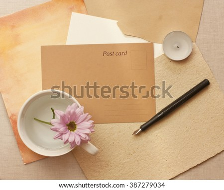 A vintage style still life with a brown paper postcard with a place for text, a tender pink chrysanthemum in a white cup, an ink pen, a candle, and some old papers, shot from above - stock photo