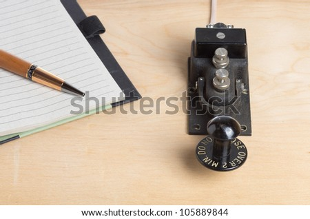 A vintage telegraph key with notebook - stock photo