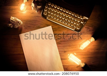 A Vintage Typewriter on a wooden table with lightbulbs and writing paper. - stock photo