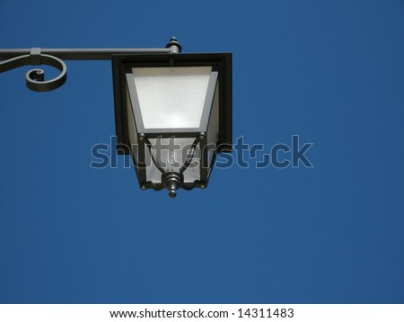 A vintage white glass street lantern on blue sky background