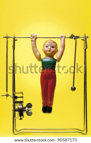 a vintage wind-up toy of trapezist or gymnast against yellow background - stock photo