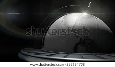 A vintage wooden world globe ornament backlit on an isolated black background - stock photo
