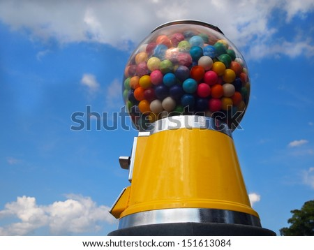 A vintage yellow gumball machine with multi-colored gumballs stands tall in front of a blue sky with wispy clouds. - stock photo