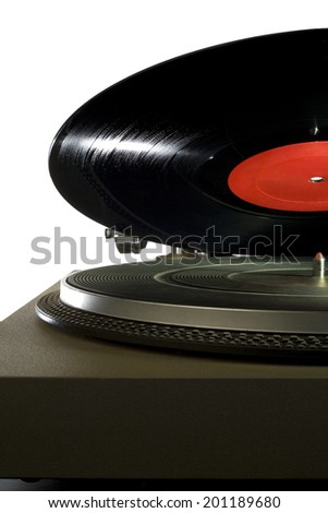 A vinyl record lowering onto a vintage record player. - stock photo