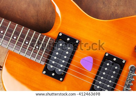 a violet guitar pick and electric guitar - stock photo
