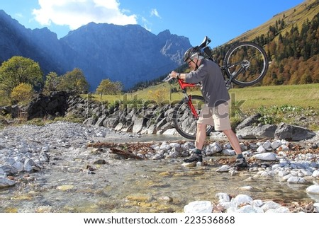 A Vital Senior shouldering a Mountainbike river crossing - stock photo