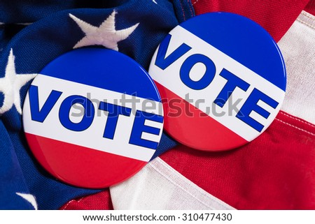 "A ""VOTE"" pin or button on a flag of the United States - stock photo"